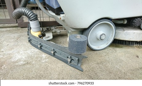 A closeup view of a walk behind electric automatic floor scrubber with front rotary brush and a squeegee at the back.