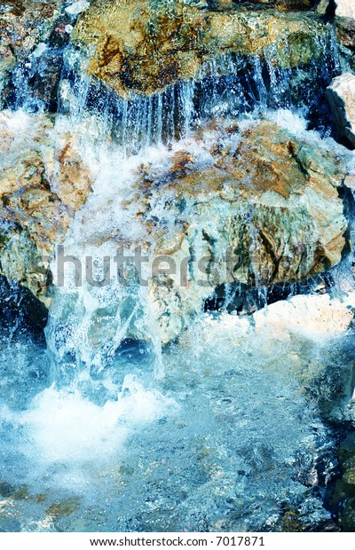 close-up view of water falling flowing over rocks into pool