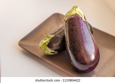 Close-up view of wet eggplants, aubergines fruit with drop water isolated on plate on white background.Raw aubergine with water drop.Wet fresh eggplant