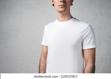 Close-up view of white blank t-shirt on young male body. Studio portrait