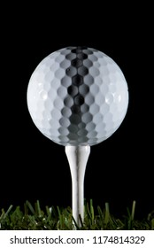 Closeup view of white golf ball laid on fixture on black background