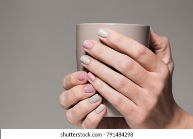 Closeup view of white hands of healthy woman with beautiful modern grey and pink manicure design. Woman holding brown cup. Horizontal color photography.