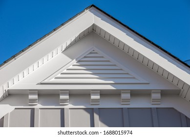 Close-up view of a white triangle gable vent above a decorative trim board on a newly built American single family home