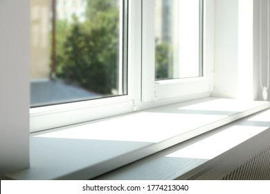 Closeup view of window with empty white sill