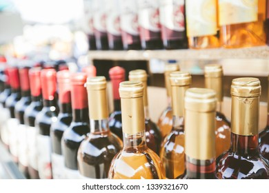 Closeup view of wine bottles in rows for sale at outdoor market
