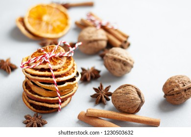 Closeup view of winter flavouring ingredients: dry orange slices, cinnamon, anise stars, walnuts.