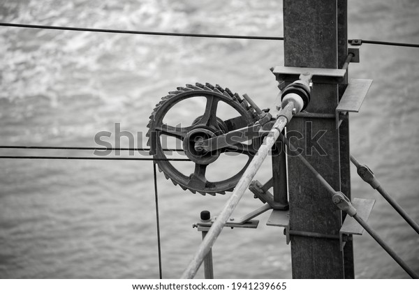 Closeup view of a wire tension wheel. Electric wire tensioner for trains, trams and trolley buses. Black and white industrial photo.