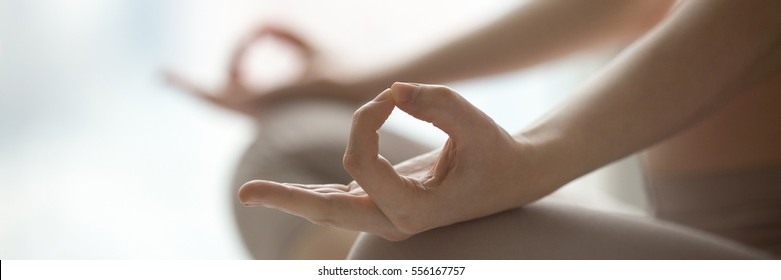 Close-up view of woman doing morning yoga after waking up at home, sitting in Easy pose, Sukhasana posture and meditating. Working out on the bed. Horizontal photo banner for website header design