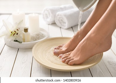 Closeup view of woman filling dish with water for foot bath indoors. Spa treatment