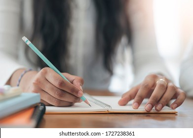 Closeup view of woman hand using  pencil writing on note pad while sitting at the table.