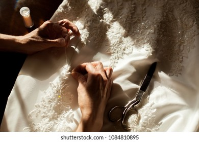 Close-up view of the woman hands sewing with the needle the beautiful wedding dress decorated with flower patterns. Sewing scissors on the dress. No face