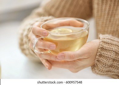 Closeup view of woman holding herbal cup of tea