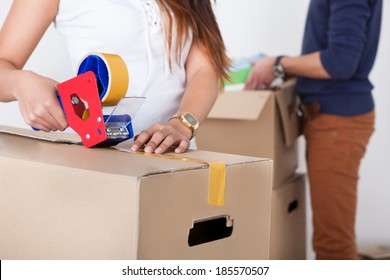 Close-up view of woman packing cardboard box with man standing in background at home