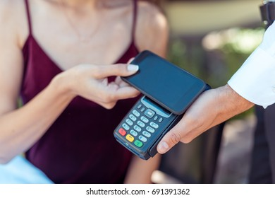 Close-up view woman paying with NFC technology on smartphone