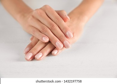 Closeup view of woman with smooth hands and manicure at table, space for text. Spa treatment