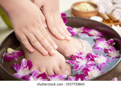 closeup view of woman soaking her hand and feet in dish with water and flowers on wooden floor. Spa treatment and product for female feet and hand spa. orchid flowers in ceramic bowl.