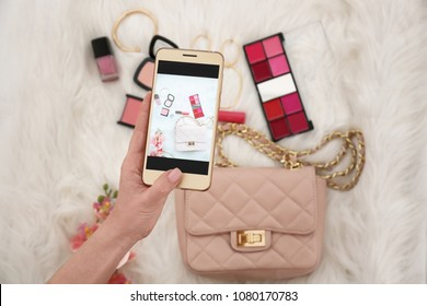Closeup view of woman taking photo of cosmetics and accessories with mobile phone