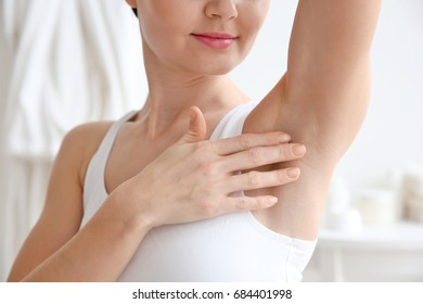 Closeup view of woman touching her armpit on blurred background. Epilation concept