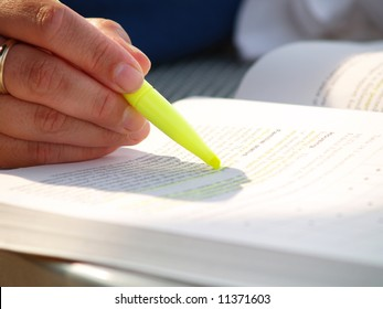 Closeup view of a woman using a highlighter while studying outside in the sunlight