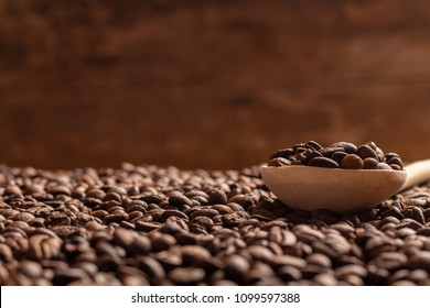 Close-up view of wooden spoon with coffee beans on blur brown background