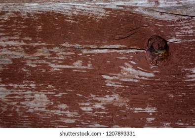 Close-up view of worn and weathered wood painted red