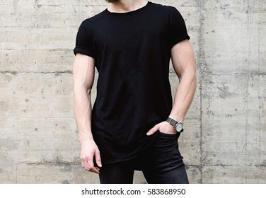 Closeup view of young bearded man wearing black tshirt and jeans posing in center of modern city. Empty concrete wall on the background. Hotizontal mockup