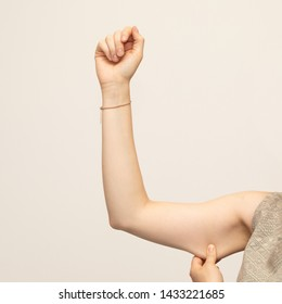 A closeup view of a young Caucasian lady squeezing her upper arm, showing the sagging skin and fat beneath the triceps, commonly referred to as bingo wings. Isolated against a white background.