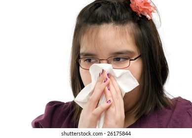 Closeup view of a young girl blowing her nose, isolated against a white background