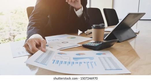 Close-up view of young handsome accountant preparing financial reports for the next meeting in modern office
