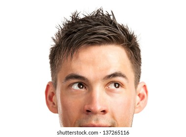 Closeup view of young man's face with his eyes looking at corner over white background