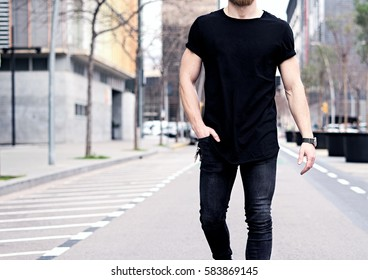 Closeup view of young muscular man wearing black tshirt and jeans walking on the streets of the modern city. Blurred background. Hotizontal mockup