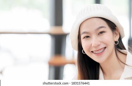 Nahaufnahme von jungen, hübschen Asiaten in Zahnstangen. Junge asiatische Frau in der Hose, die Wolle trägt, die lächelt und die Kamera anschaut.