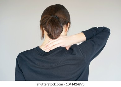 Close-up view of a young redhead woman with pain in the neck on gray background. Body And Health Care Concept.