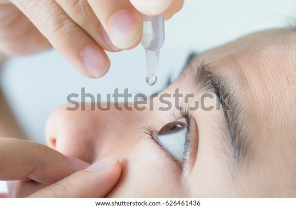年轻女子的特写视图应用眼水,人造眼泪。
