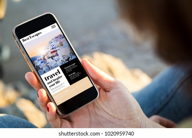 close-up view of young woman browsing travel website her mobile phone. All screen graphics are made up.
