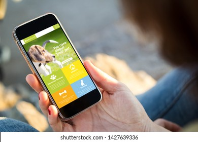 close-up view of young woman browsing pet website on her mobile phone. All screen graphics are made up.