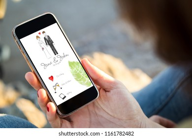 close-up view of young woman checking wedding website her mobile phone. All screen graphics are made up.