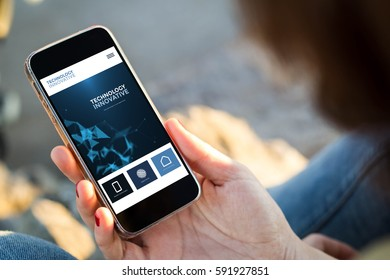close-up view of young woman checking her mobile phone. All screen graphics are made up.