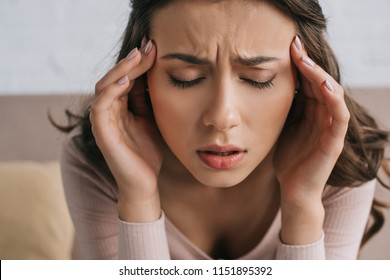 close-up view of young woman with closed eyes suffering from headache