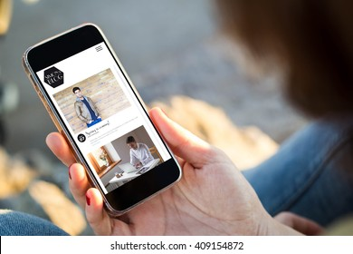 close-up view of young woman with fashion blog on  her mobile phone. All screen graphics are made up.