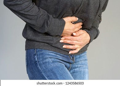 Close-up view of a young woman having painful stomachache isolated on gray background. Chronic gastritis. Body And Health Care Concept.