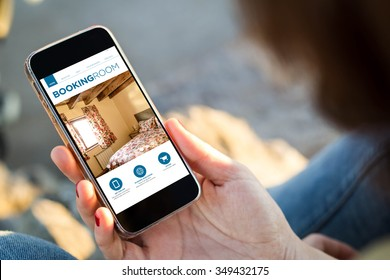 close-up view of young woman holding a smartphone with booking room app on screen. All screen graphics are made up.