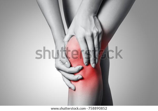Detailní pohled na mladou ženu s bolestí kolena na šedém pozadí. Černá a bílá fotografie s červenou tečkou.