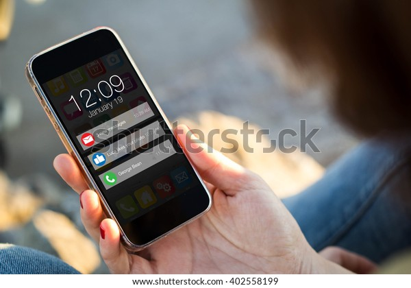 close-up view of young woman looking at notifications on her mobile phone. All screen graphics are made up.