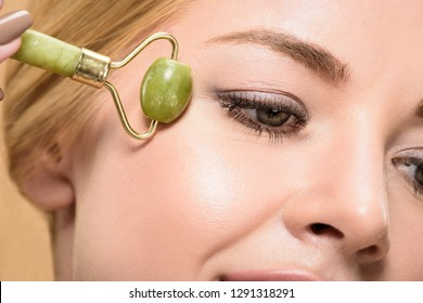 close-up view of young woman massaging face with jade roller isolated on beige