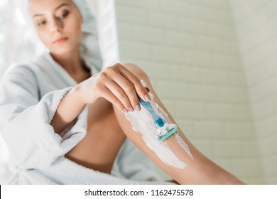 close-up view of young woman shaving leg in bathroom
