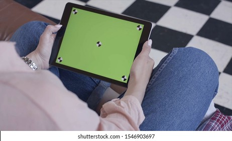 Close-up view of young woman sitting on the chair and looking on the tablet with chroma key green screen. Stock footage. Chroma key screen for placement of your own content.