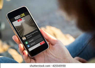 close-up view of young woman watching a live video on her mobile phone. All screen graphics are made up.