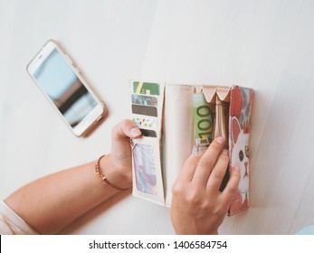 Closeup view of a young woman's hands holding an open wallet with money, credit, debit cards for paying, shopping. With a cell phone, smartphone on the table.