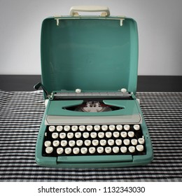 Closeup of vintage aqua, teal coloured typewriter. Retro office writers desk. Antique machine for typing letters or creative pages. Journalist workspace, top view.